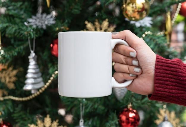 Женщины вручают держать белую керамическую кофейную чашку на предпосылке рождественской елки. макет для креативного рекламного текстового сообщения или рекламного контента.