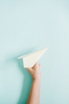Women hand holding white paper plane on pale blue
