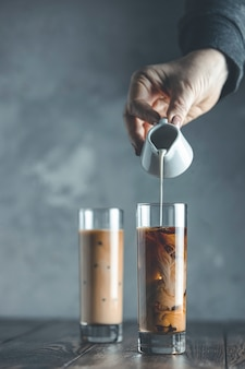 Women hand is pouring homemade sour cream from small jar to glass with brew cold coffee and ice. cold summer drink on a dark wooden table and gray background with copy space