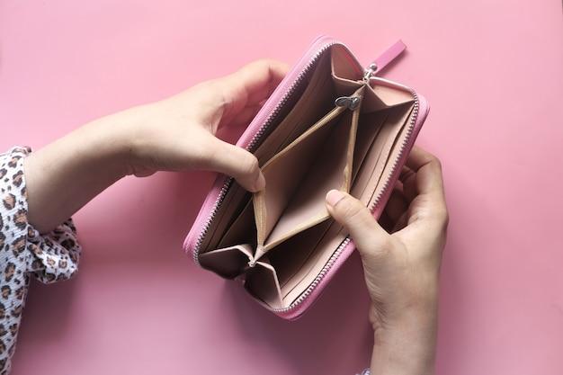 Руки женщины открывают пустой бумажник на розовой поверхности.