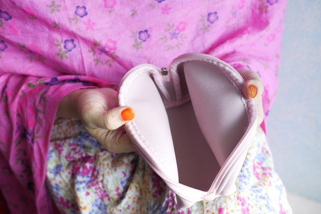 女性はピンクの表面に空の財布を手で開きます