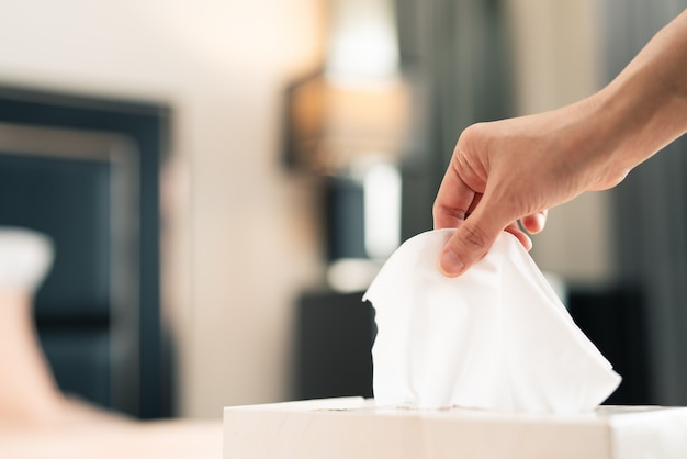 Women hand picking tissue paper from the tissue box