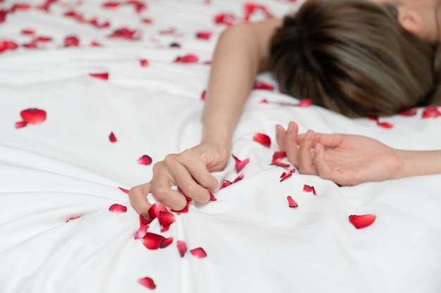 Women hand pulling or grasping white sheets. hand sign orgasm of woman on white bed sheet with rose petals.