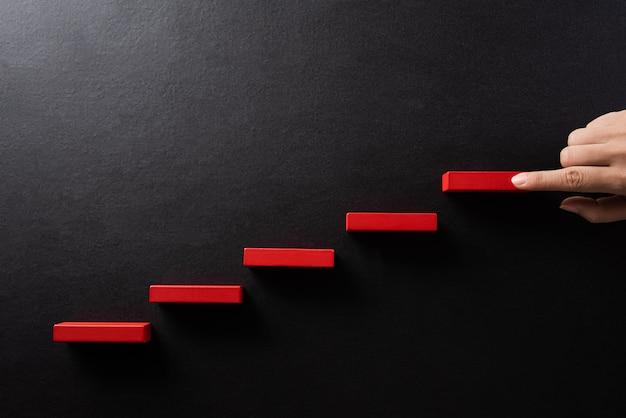 Женская рука положила красный деревянный блок в виде лестницы
