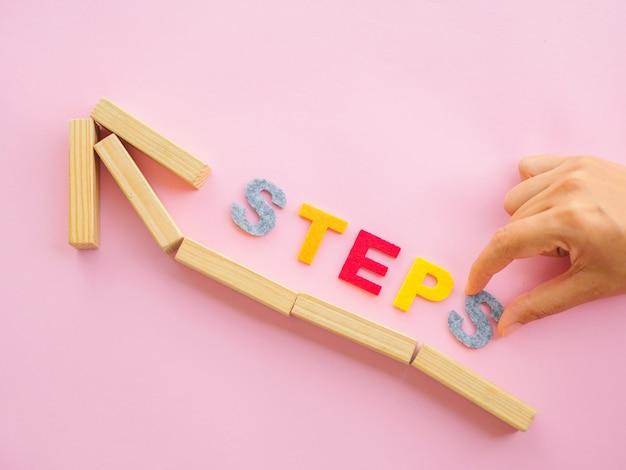 Женщины кладут деревянные блоки в форме стрелы. шаг вверх стрелка лестницы