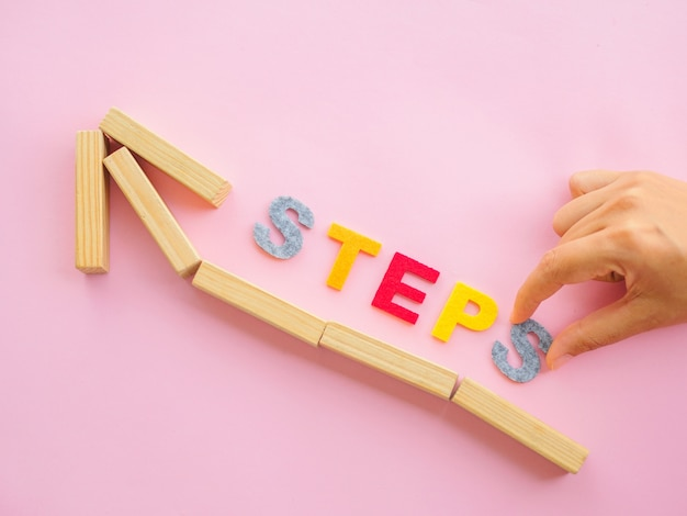 Women hand put wooden blocks in the shape of arrow. step up arrow stairs