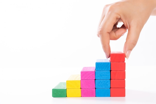 Women hand put wooden blocks in the shape of a staircase.
