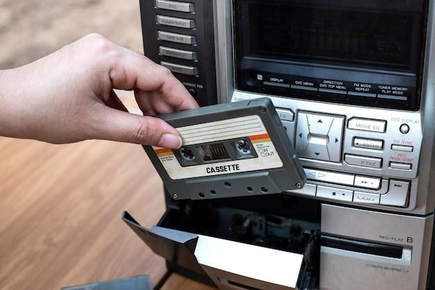 昔ながらのオーディオテーププレーヤーにカセットを入れる女性の手