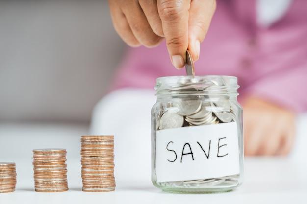女性はお金を節約するためにガラスの瓶にお金のコインを入れて手渡します。お金と財務の概念を節約する