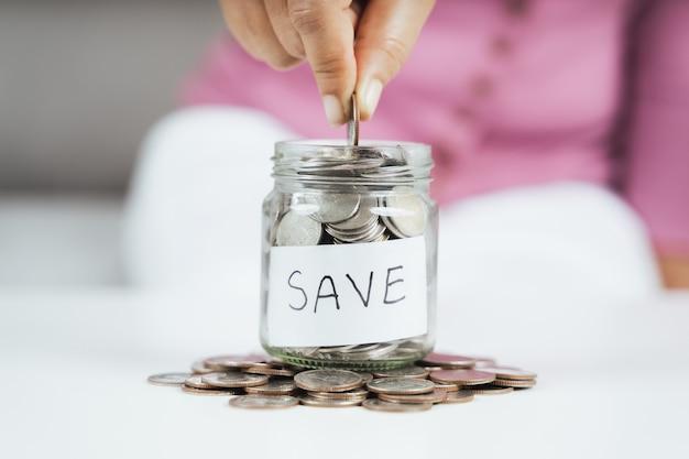 여성들은 돈을 절약하기 위해 유리병에 동전을 넣고 있습니다. 돈과 금융 개념을 절약