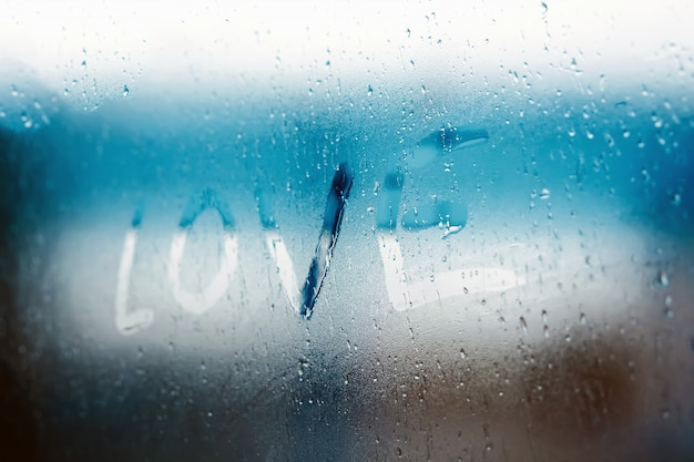 Women hand's drawing love word on glass window with water drop concept design
