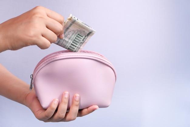 女性の手で白で分離された財布に現金を節約