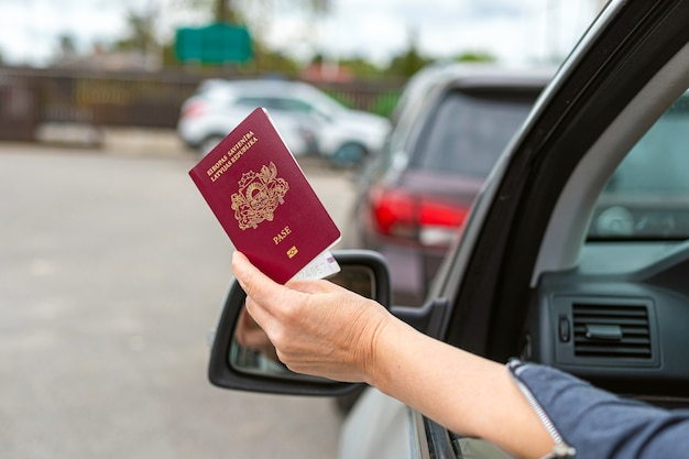 Women hand through car window giving passport for customs control, driver with an identity card in a car at a border checkpoint