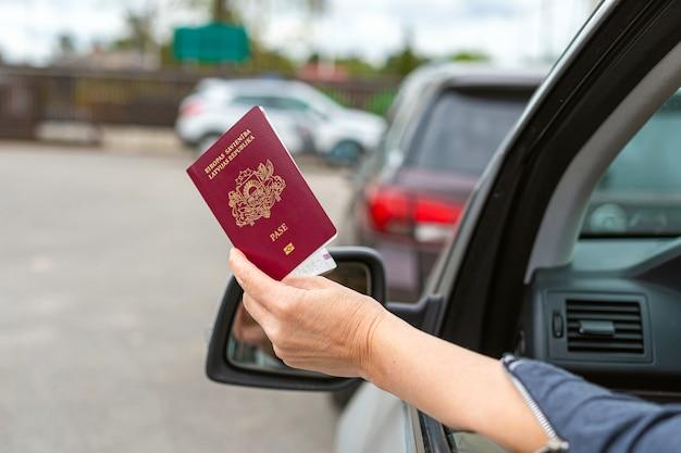 女性が車の窓から通関手続き用のパスポートを渡し、国境検問所で車に身分証明書を持っている