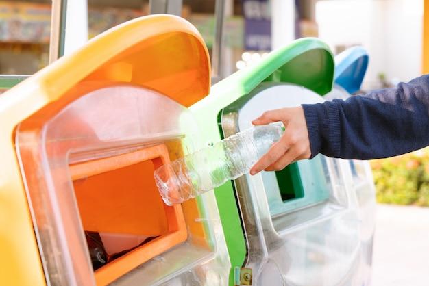 Женская рука выбрасывает мусор в мусорное ведро / мусор, сортируя отходы / мусор, прежде чем бросить в мусорное ведро