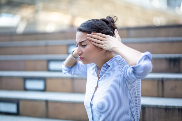 女性の手が頭痛で彼女の頭に触れています。