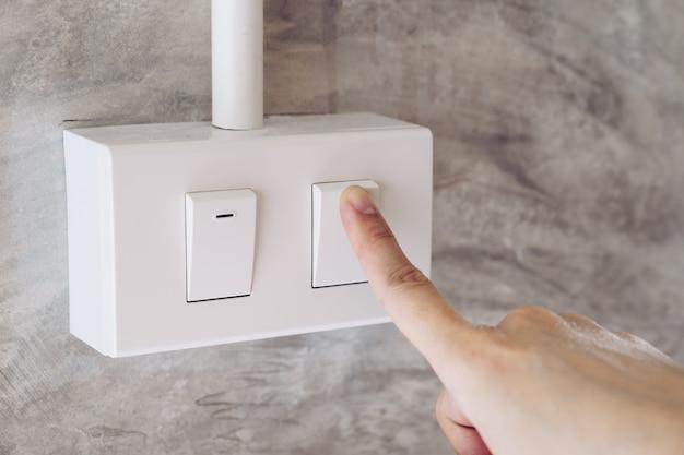 女性の手がセメントの壁の背景に電気スイッチをオンにします