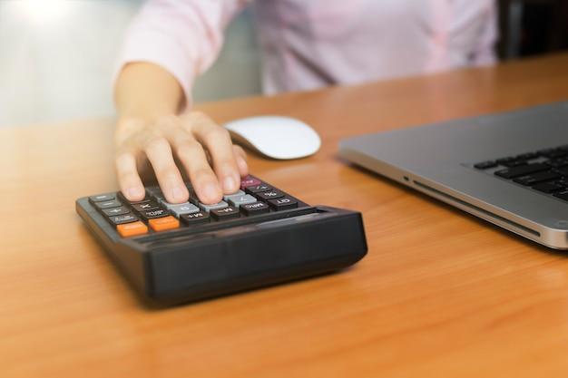 オフィスの机の上の電卓を使用して女性の手。女性のハンドプレス電卓。オフィスで電卓を使用してビジネスの女性の手。木のテーブルの家計計算。