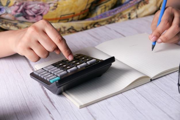 Женщины рука с помощью калькулятора на офисном столе