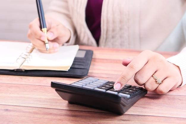 女性の手はオフィスの机の上の計算機を使用して