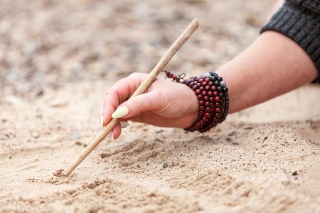 木の棒で砂に書くブレスレットと女性の手