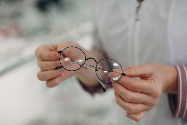 Женщины рука с линзами модных очков. очки прозрачные диоптрийные.