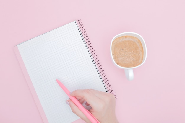 Женщины рука с записью на бланке записной книжки на розовой стене, instagram и бизнес-концепции.