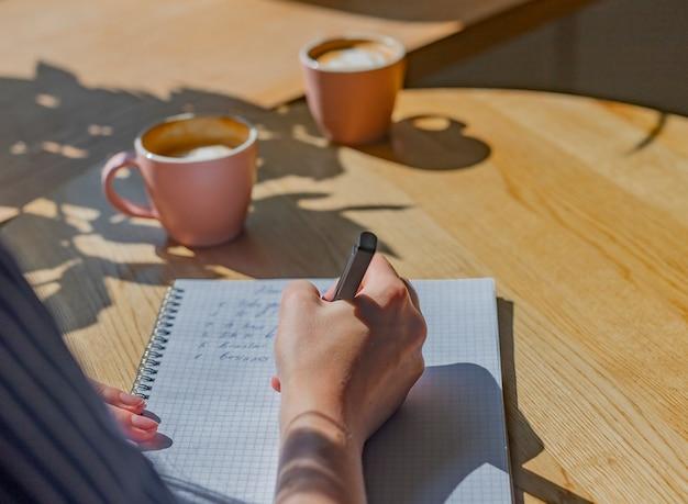 Женщины пишут планы в блокноте или ежедневнике над деревянным столиком в кафе с солнечным светом из окна и ...