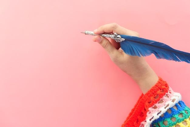 Женщины почерков с авторучкой на розовом фоне.