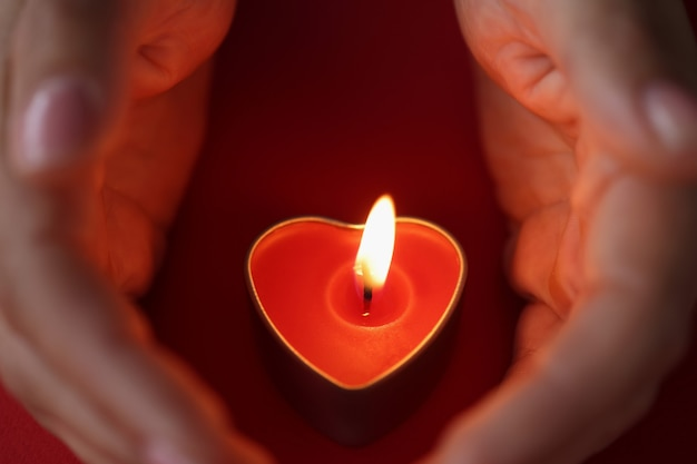 Women hands carefully protect candles in form of heart with burning fire scented candles for