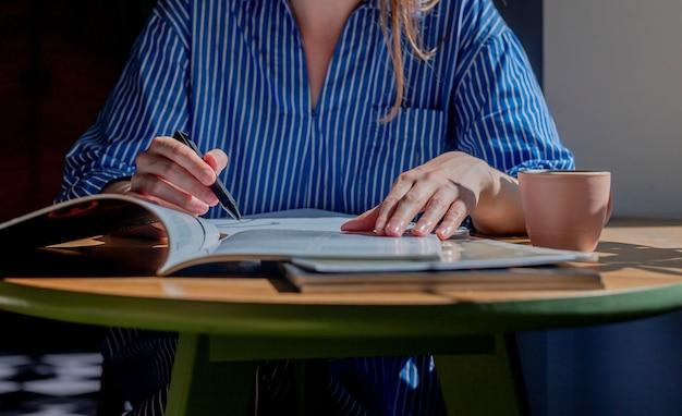 Женщины руки крупным планом писать ручкой в блокноте, делая заметки из книги, изучая учебник и ...