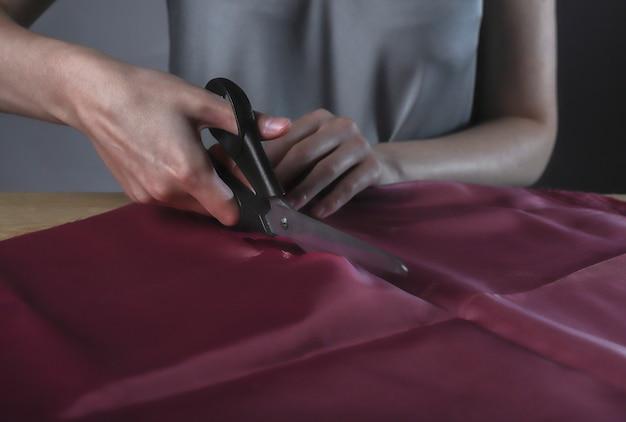 Женские руки режут глянцевую красную ткань швейными ножницами, портниха работает
