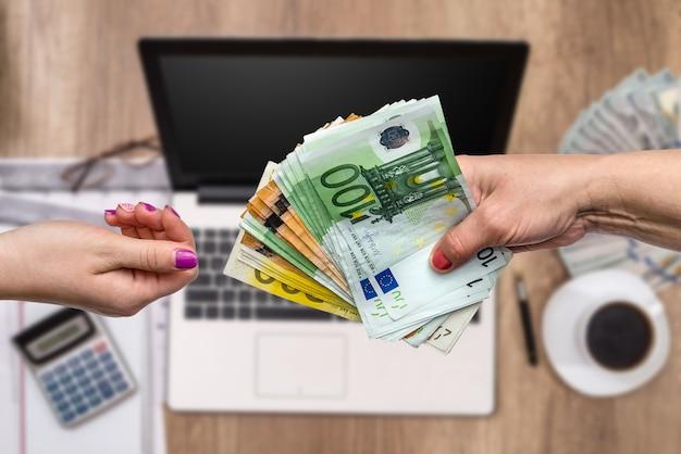 Руки женщины обмениваются банкнотами евро крупным планом