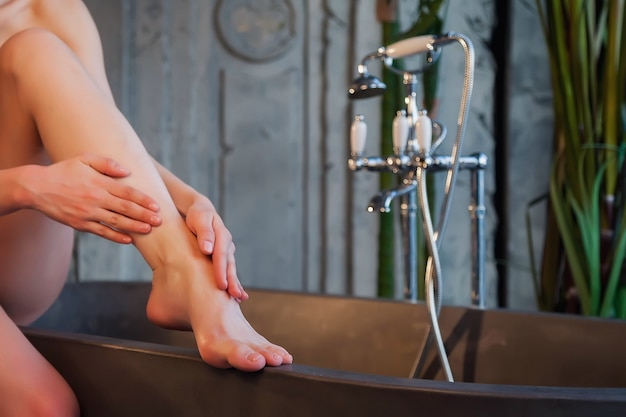 Women hands do foot massage with cosmetic oil for applying drops to skin in bath. female applies oil in background of an old interior bathroom. concept of healthy lifestyle and self care. copy space