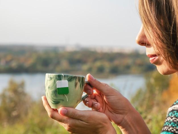 Женские руки держат фарфоровую кружку с мешочком внутри, пьют горячий зеленый чай на природе. женщина наслаждается теплым варевом или напитком в чашке, расслабляется отдыхом, отдыхая на улице.