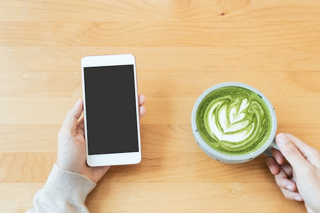 Women hands hold a cup of green tea latte while using phone technology, beverage, lifestyle concept