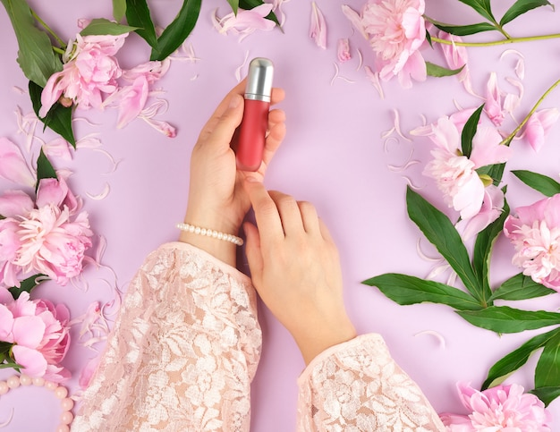 Women hands hold red lipstick, purple background with blooming pink peonies