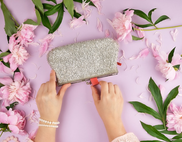 Women hands hold a silver clutch with cosmetics