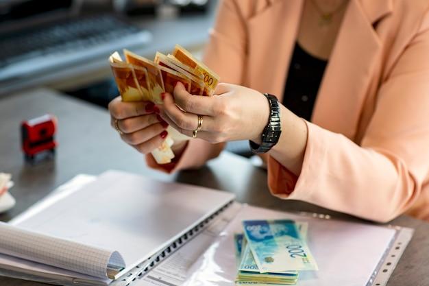 이스라엘 새 셰켈의 부채를 들고 있는 여성의 손. 테이블에 흩어져있는 돈의 스택. 손의 자른 이미지는 지폐를 보유하고 있습니다. 선택적 초점입니다. 돈 배경입니다. 금융 개념