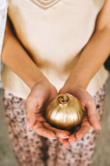 結婚指輪が付いた金色の小さなカボチャを持った女性の手。結婚式の要素、詳細、装飾。上面図。