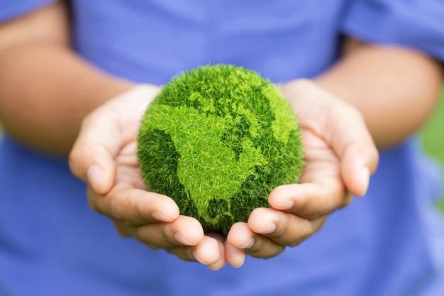 녹색 배경에 지구를 들고 여자 손 저장 및 보호 지구