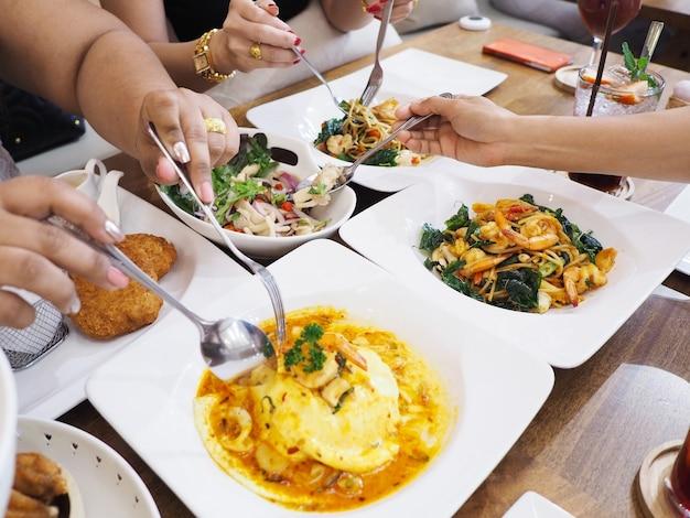 フォークとスプーンを持って、モダンなレストランでスパイシーなタイ料理のディナーパーティーを選ぶ女性の手。
