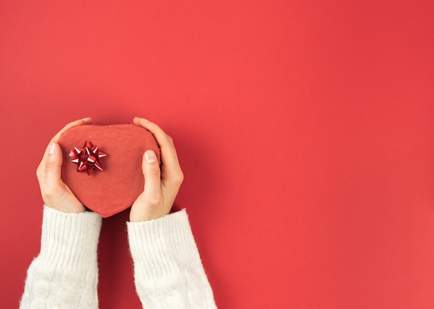Women hands holding heart-shaped box on red background. valentine day