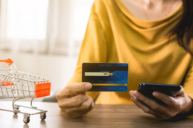 Women hands holding mobile phone with blank screen and credit card on office desk and using mobile phone for online shopping, internet banking, online trading