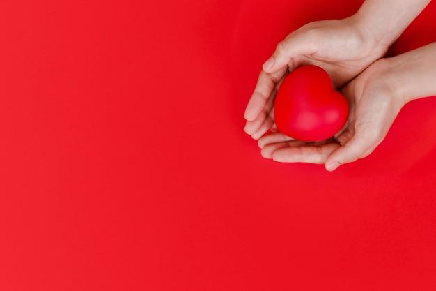 Женские руки держат красное сердце на красном