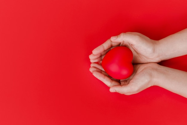 Women hands holding red heart on red