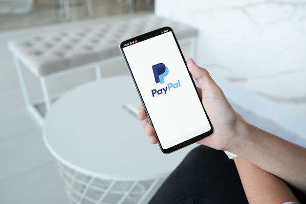Women hands holding smartphone with paypal apps on the screen. paypal is an online electronic payment system.