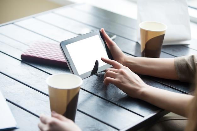 女性の手は、カフェで白い空の画面とタブレットを持っています。閉じる