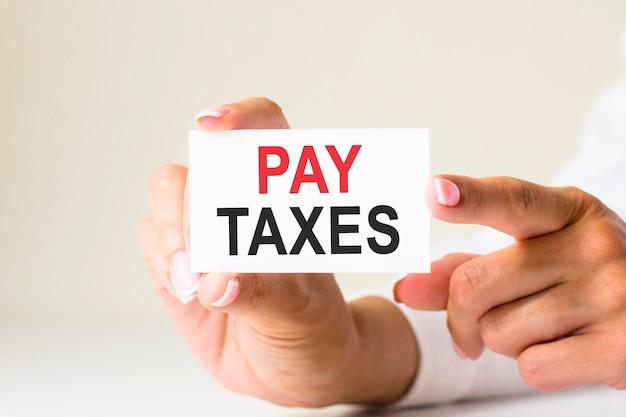여성의 손에는 세금을 지불하라는 텍스트가 있는 백서가 있습니다. 노란색 배경입니다. 비즈니스, 마케팅, 금융 개념에 사용할 수 있습니다.