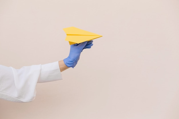 女性はベージュの背景に黄色い紙飛行機を保持している保護用の青いラテックス手袋を手渡します。コピースペース